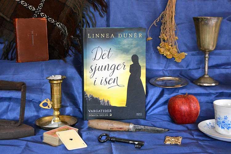 Boken Det sjunger i isen av Linnea Dunér, omgiven av föremål ur berättelsen.