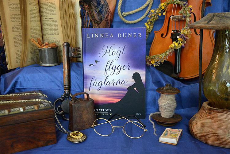 Historiska romanen Högt flyger fåglarna av Linnea Dunér, omgiven av föremål ur berättelsen
