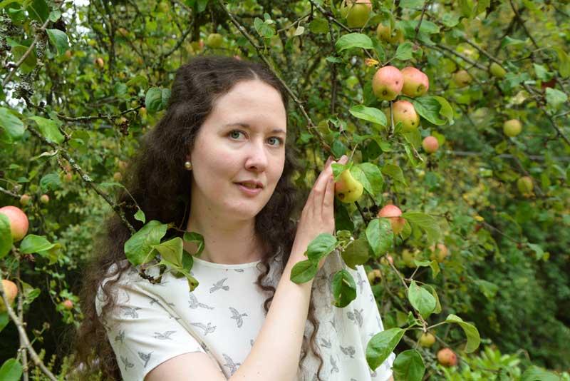 Linnea Dunér står vid ett äppelträd