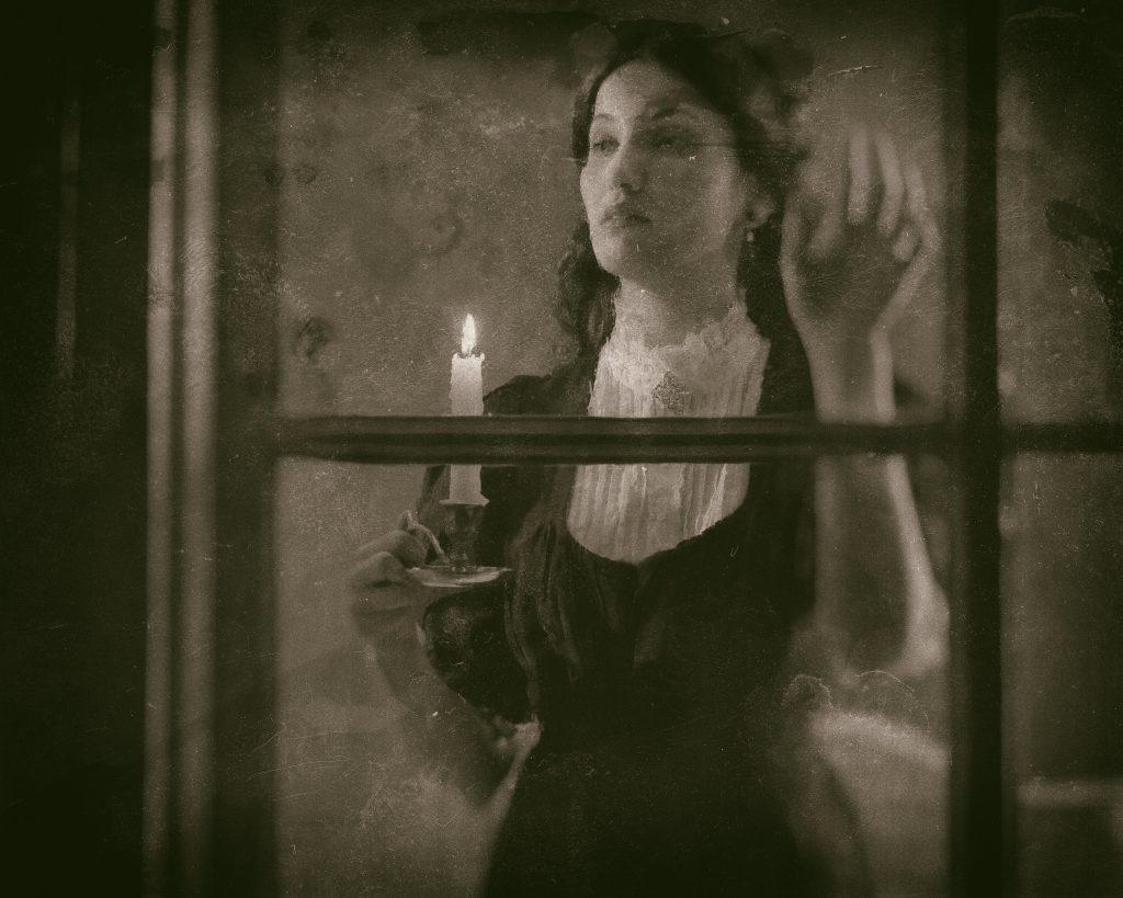 Foto i gråskala av en yngre kvinna i gammaldags kläder som står innanför ett fönster med ett ljus i handen.