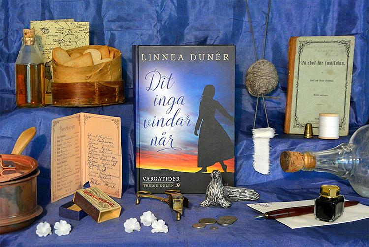 Historiska romanen Dit inga vindar når omgiven av föremål ur berättelsen, som flaskor, mynt, sybehör, en tändsticksask, en läsebok, en karta, en ask med kakor och ett dansprogram.