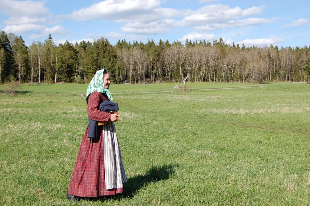 Linnea Dunér i rödrutig 1800-talsklänning, förkläde och sjalett