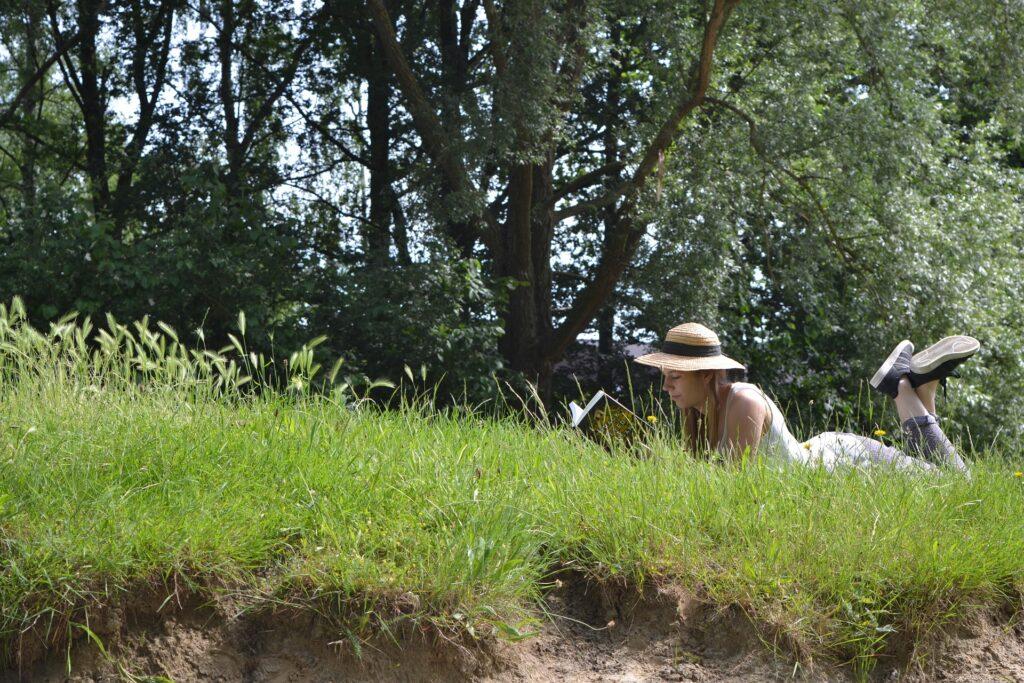 Kvinna som ligger och läser i gräset – kanske en bok av en egenutgivare?