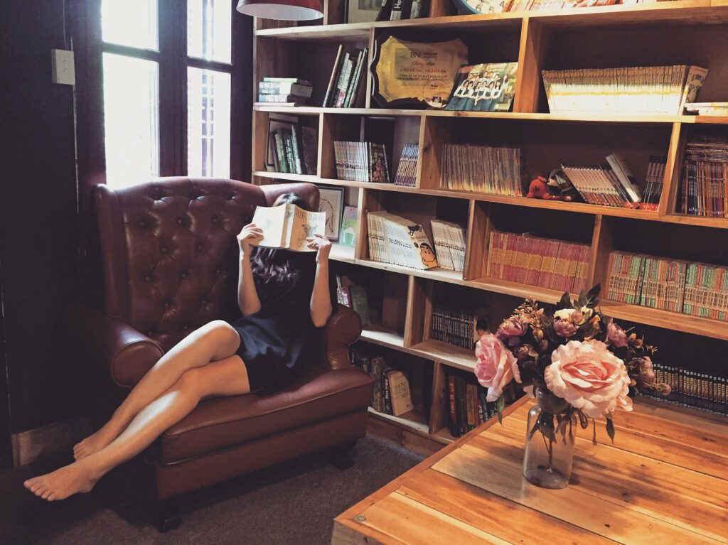 Kvinna som sitter i en fåtölj med en bok bredvid en bokhylla full med böcker.